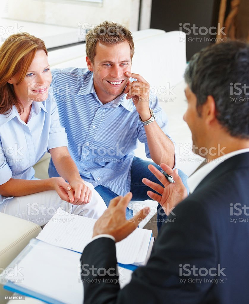 Happy couple discussing financial matter with consultant royalty-free stock photo