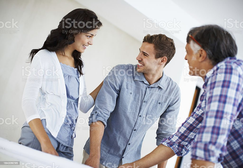 Happy couple discussing with architect royalty-free stock photo