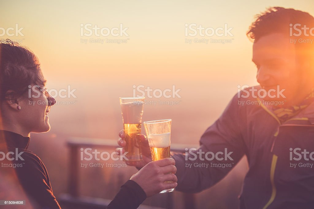 Happy Couple Drinking Beer after Cross-Country Running, Alps, Autumn, Europe stock photo