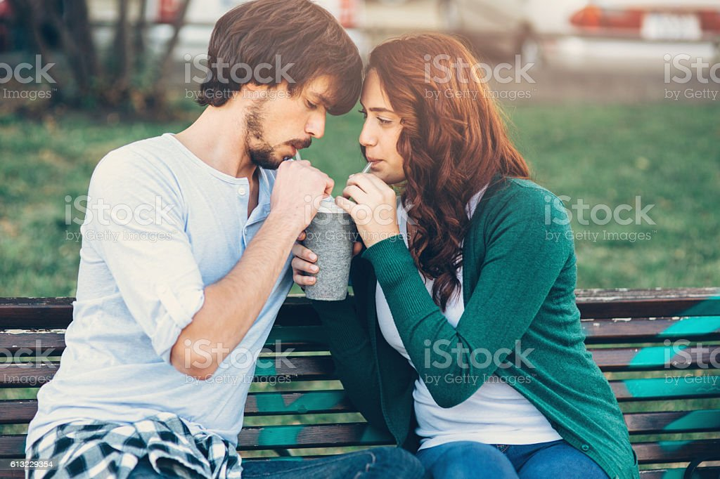 Happy couple drinking from one cup stock photo