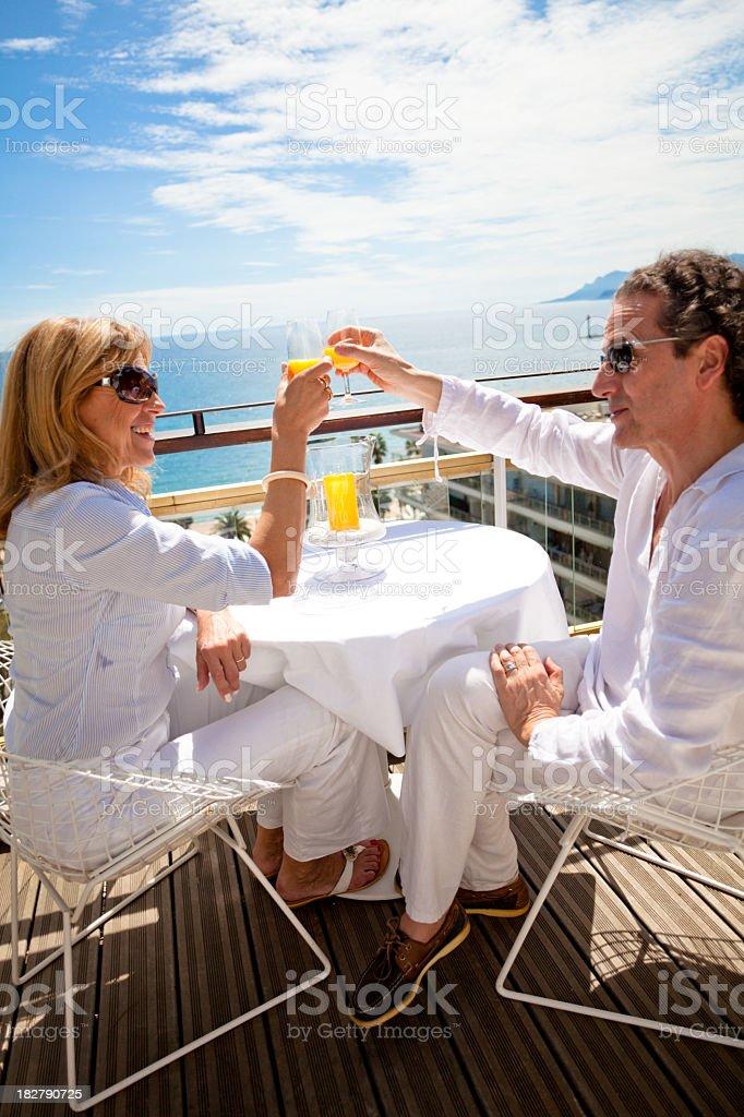 Happy couple drinking mimosas on a penthouse balcony royalty-free stock photo