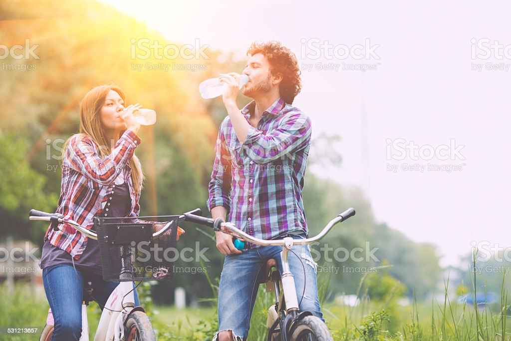 Happy Couple Drinking Water After Riding Bicycles. stock photo