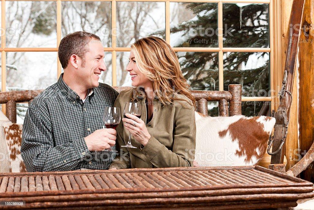 Happy Couple Drinking Wine in Ski Lodge royalty-free stock photo