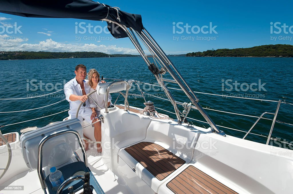 Happy couple driving a sailboat stock photo
