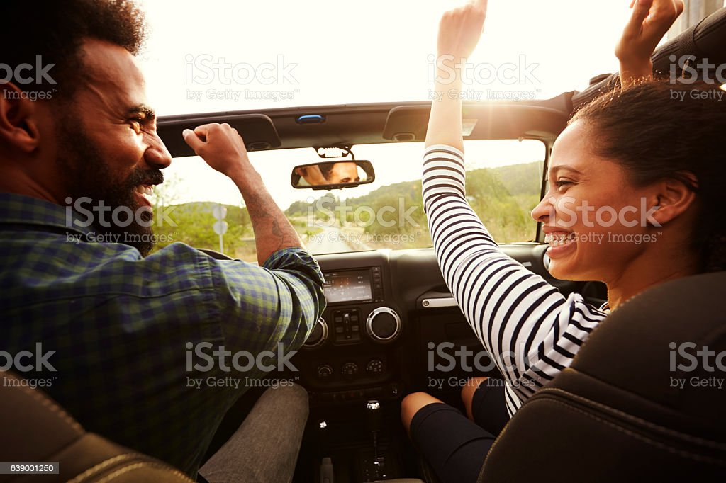 Happy couple driving in their car with arms in the air stock photo