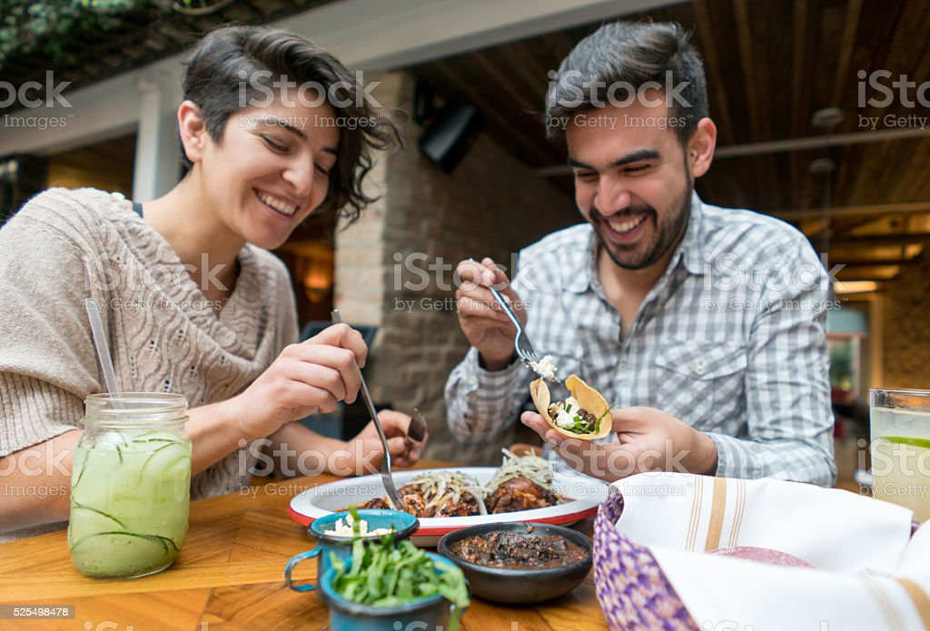 Happy couple eating at a restaurant stock photo