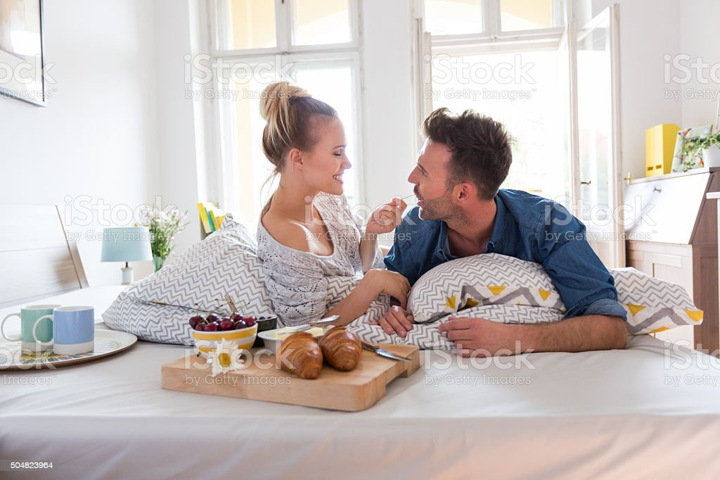 Happy couple eating breakfast in the bed at home stock photo