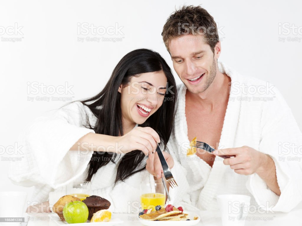 Happy couple eating breakfast together smiling royalty-free stock photo