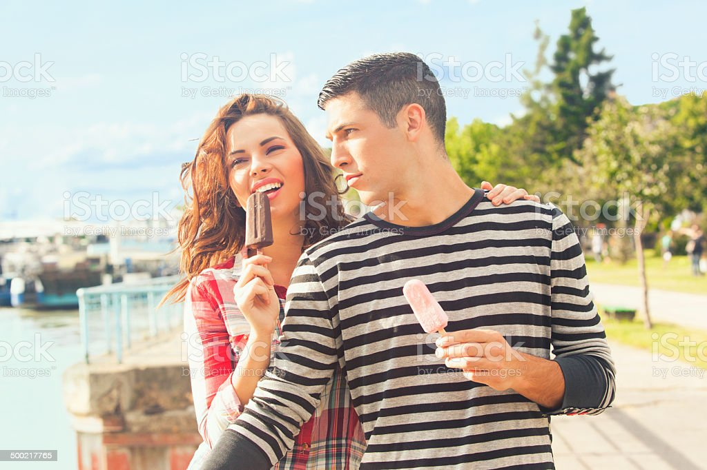 Happy couple eating ice cream outdoors on a sunny day stock photo