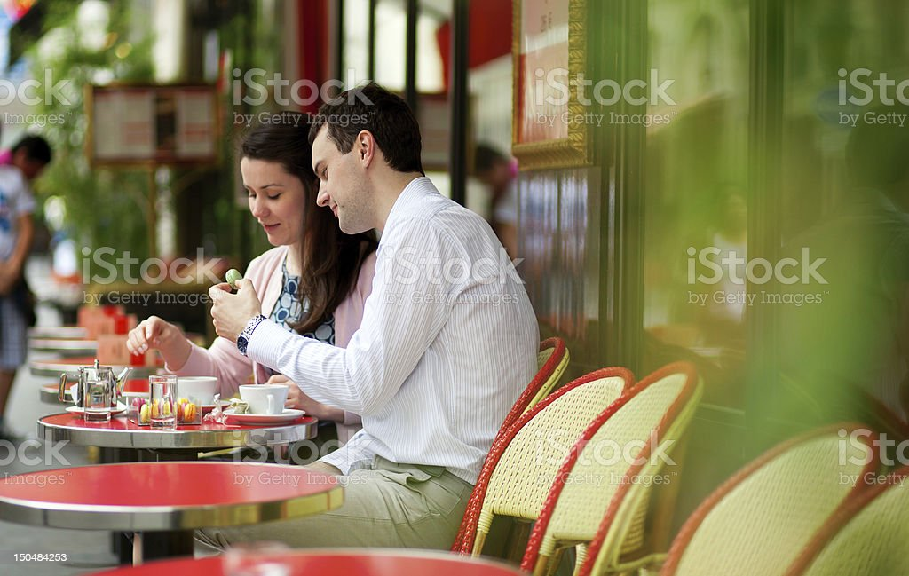 Happy couple eating macaroons in a Parisian outdoor cafe stock photo
