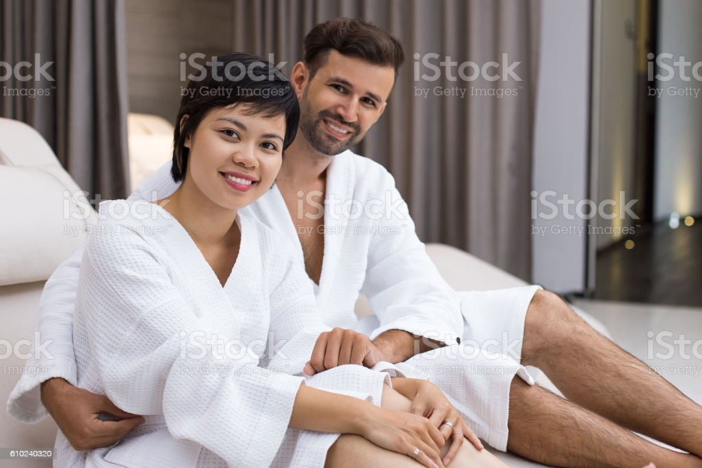 Happy couple embracing on deckchair in spa stock photo