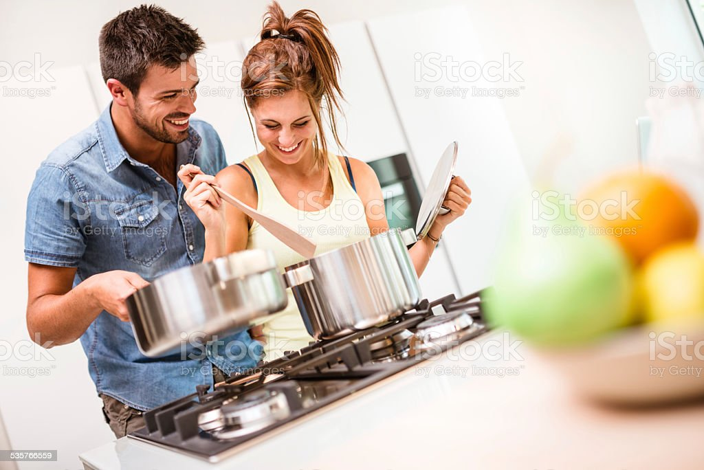 Happy couple embracing together on the kitchen stock photo
