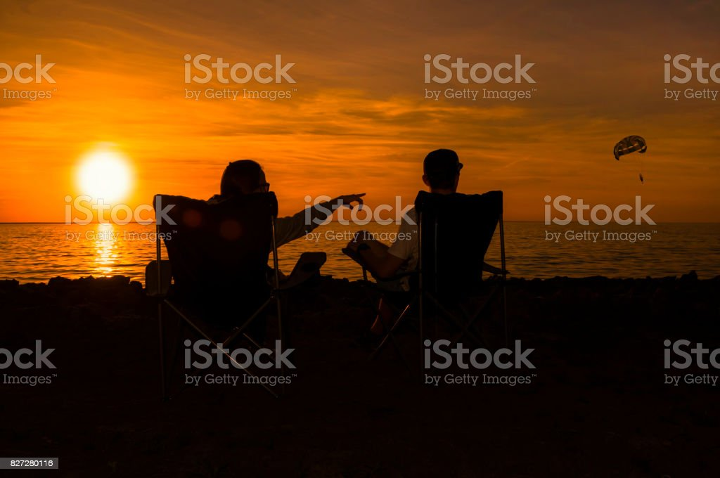 Happy couple enjoy luxury sunset on the beach during summer vacations stock photo