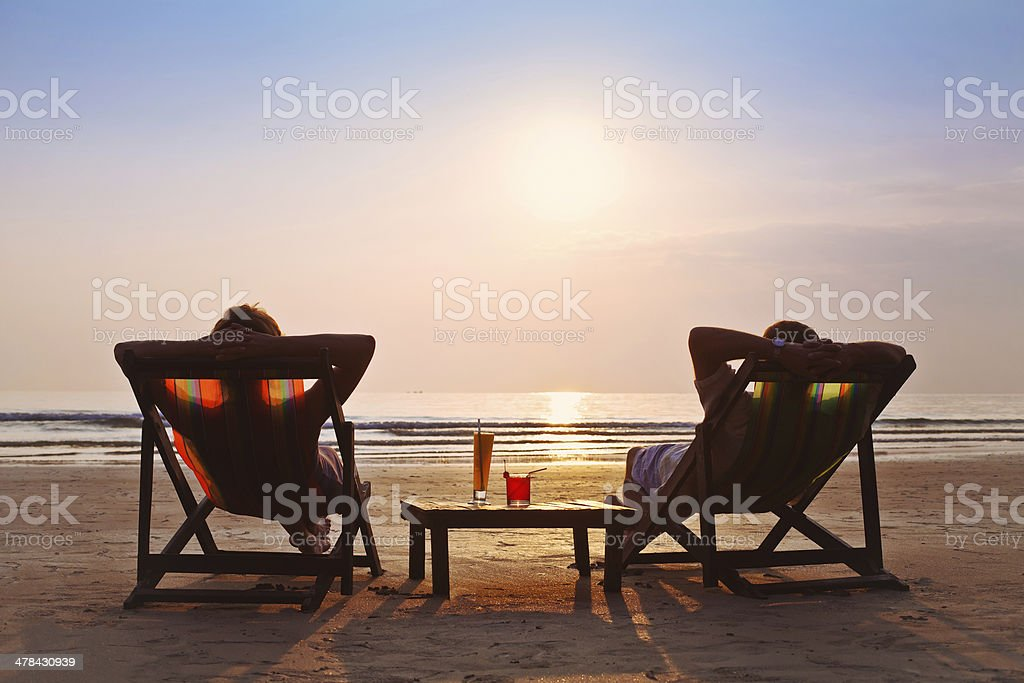 happy couple enjoy sunset on the beach stock photo