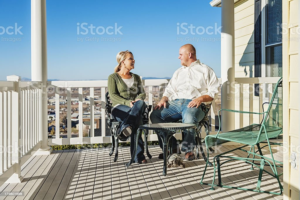 Happy Couple Enjoying a Sunny Day on Covered Porch royalty-free stock photo