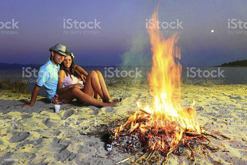 Happy couple enjoying next to the campfire on beach. royalty-free stock photo