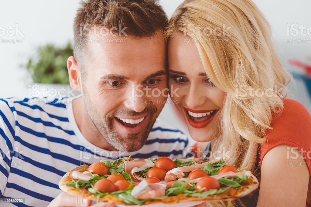 Happy couple enjoying pizza stock photo