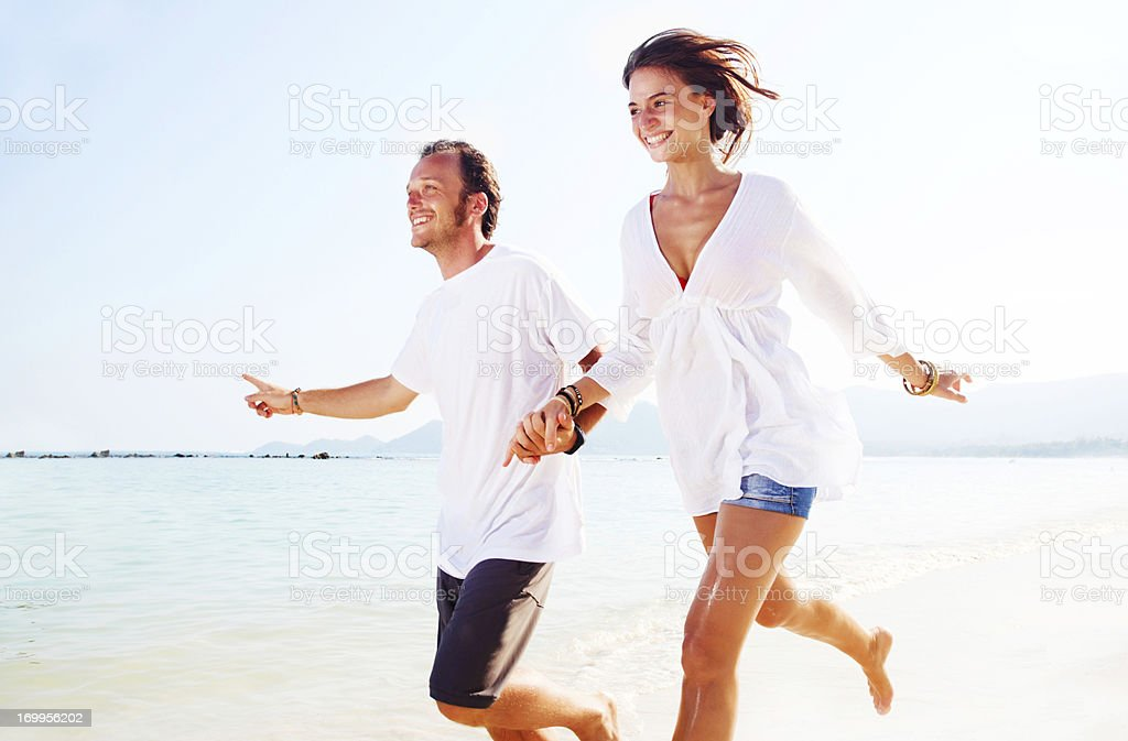 Happy couple enjoying running and holding hands on the beach. royalty-free stock photo