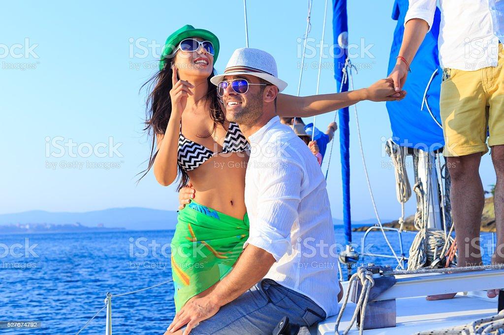 Happy couple enjoying sailboat trip stock photo