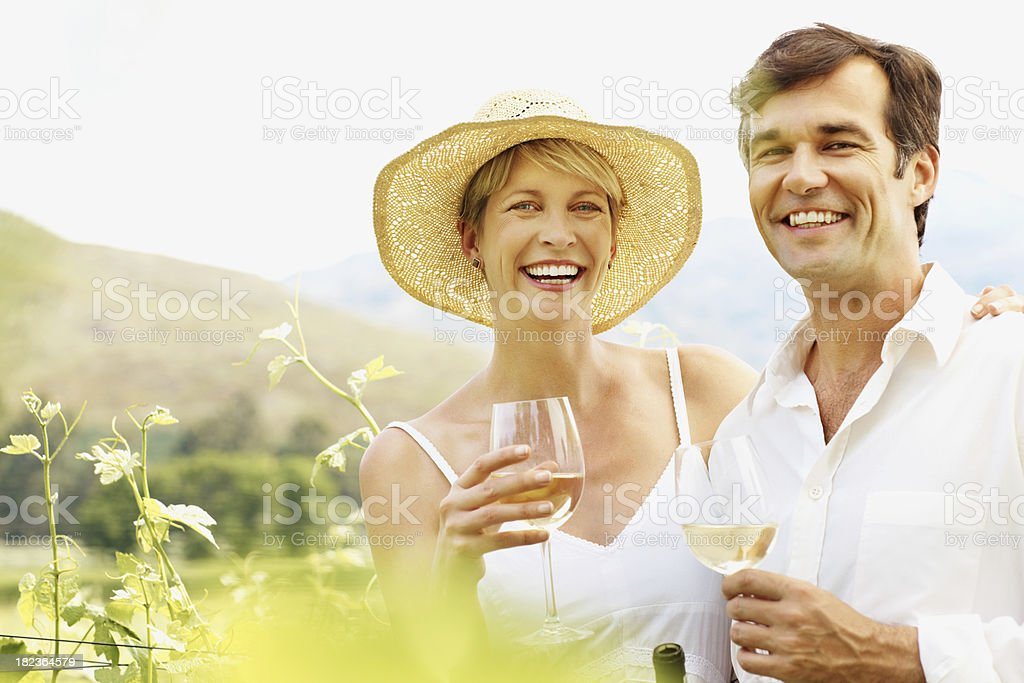 Happy couple enjoying wine in a vineyard royalty-free stock photo