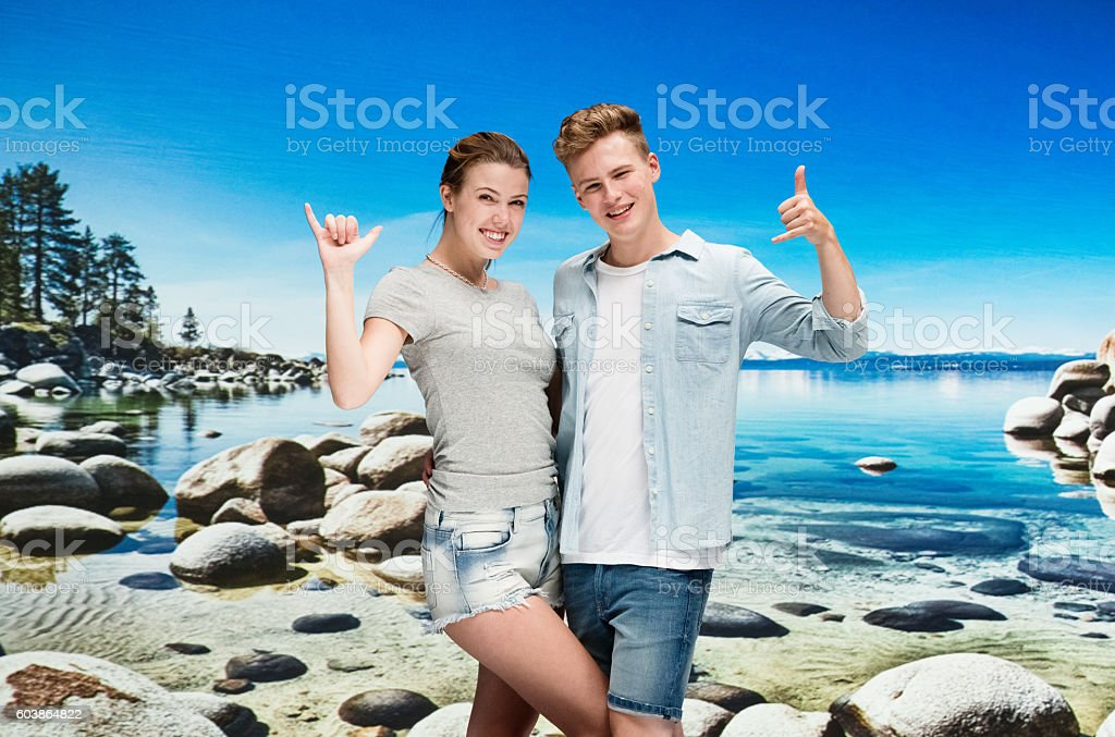 Happy couple giving shaka sign at the beach stock photo