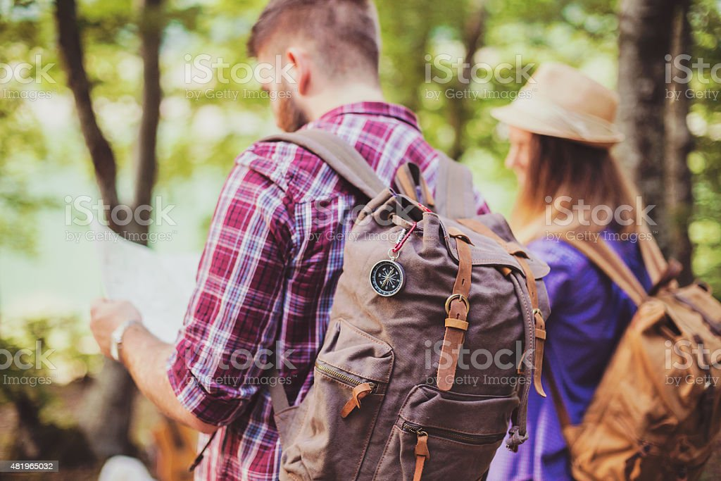 Happy couple going on a hike together in a forest. stock photo
