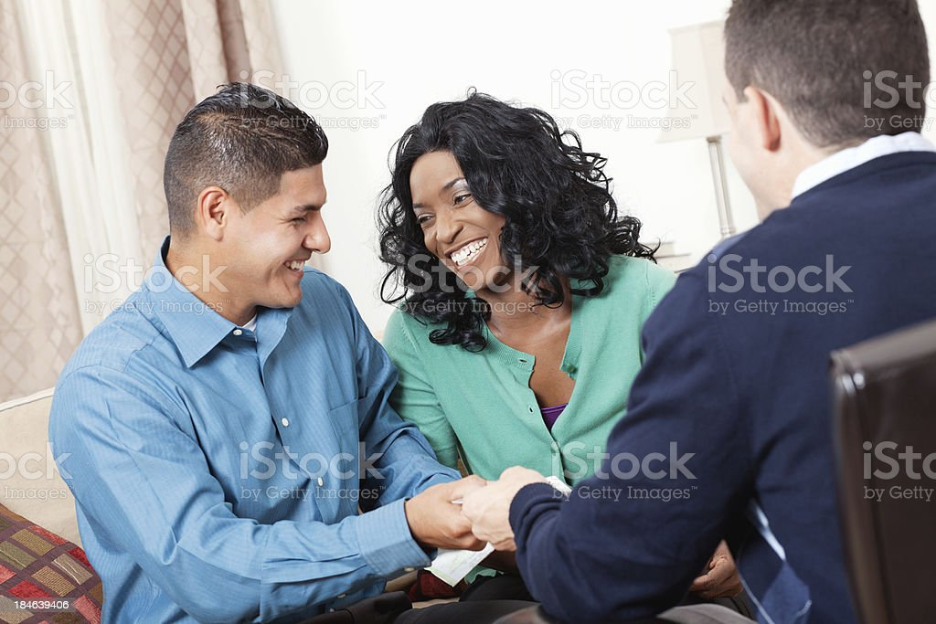 Happy couple handing over credit cards to financial counselor royalty-free stock photo
