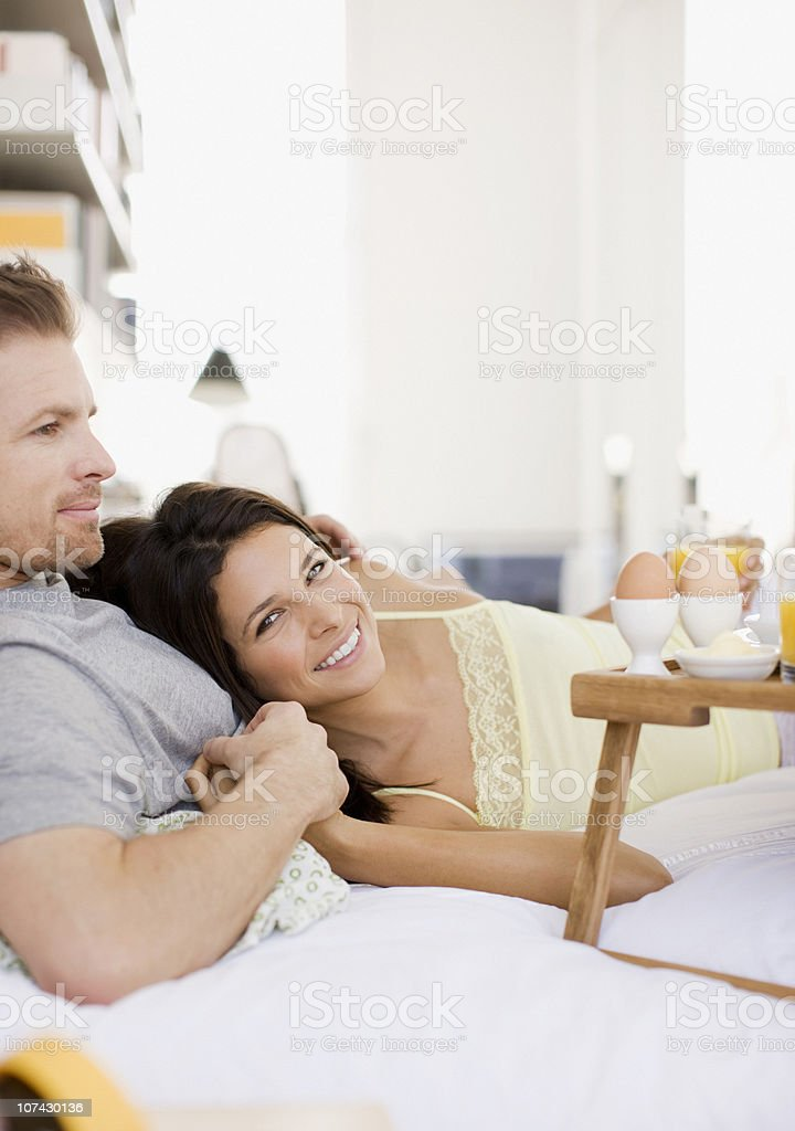 Happy couple having breakfast in bed royalty-free stock photo