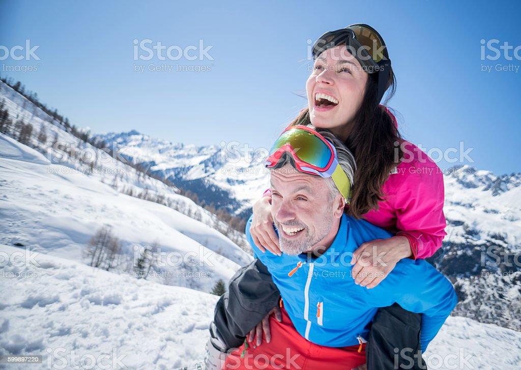 Happy couple having fun skiing stock photo