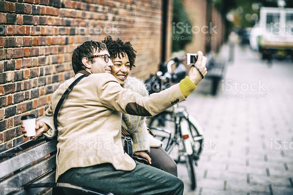 Happy couple having fun taking selfie with compact camera stock photo