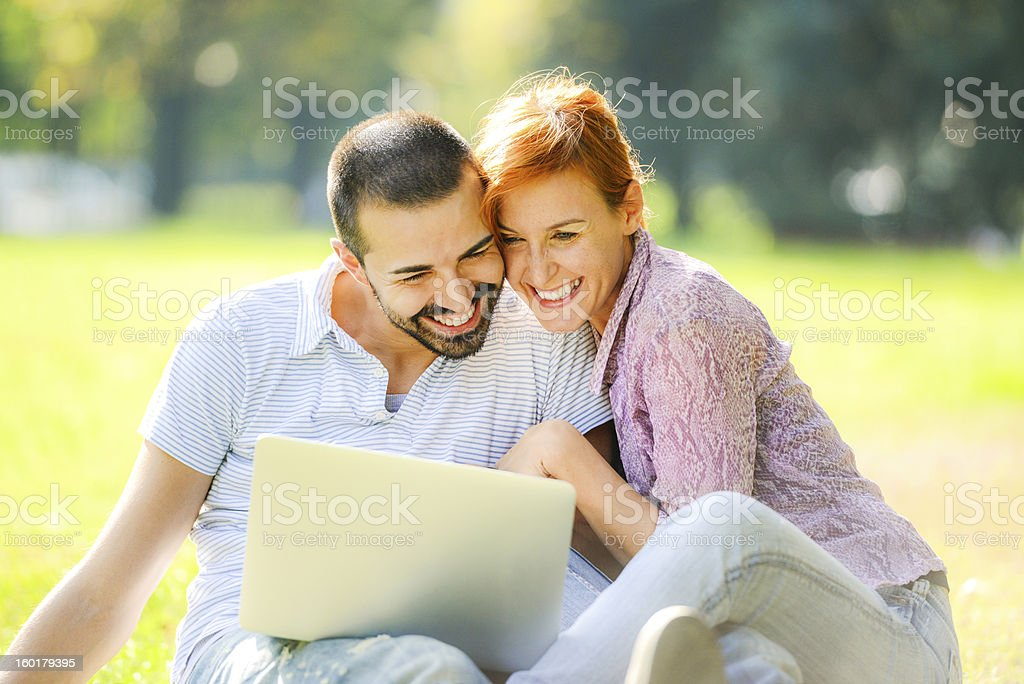 Happy Couple having fun using Laptop outdoors stock photo