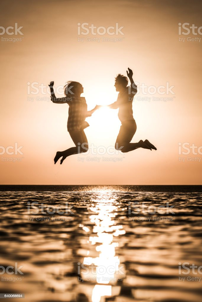 Happy couple having fun while jumping at infinity pool. stock photo