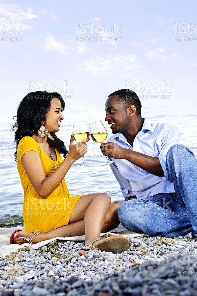 Happy couple having wine on beach royalty-free stock photo