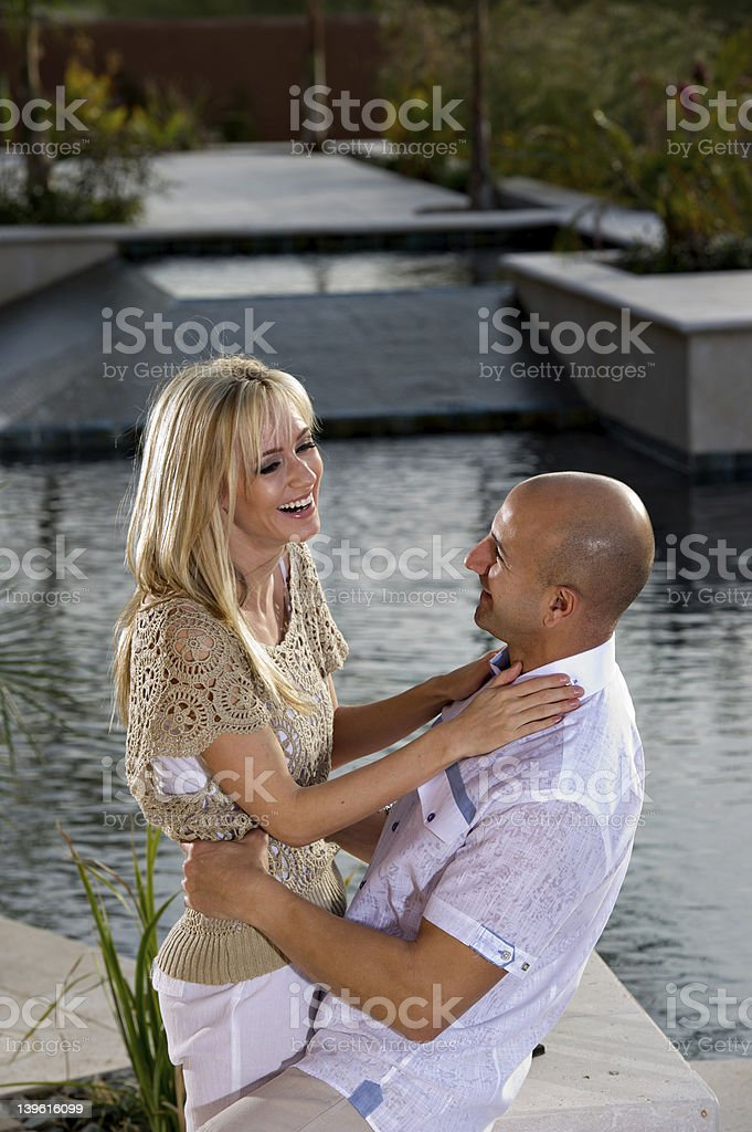 Happy couple holding each other by the pool stock photo