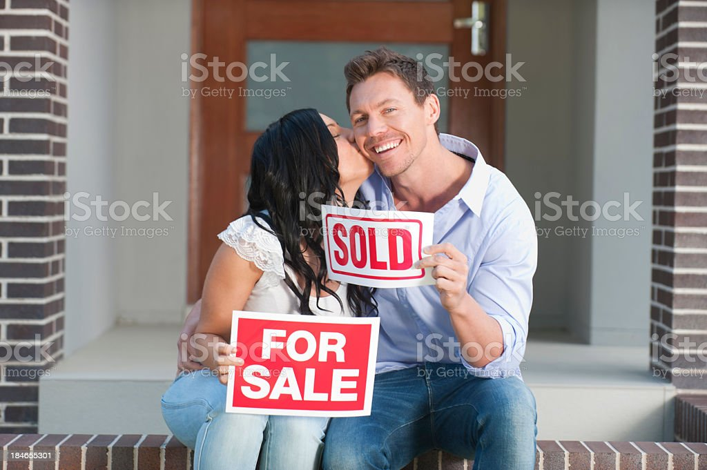 Happy couple holding for sale and sold signs kissing royalty-free stock photo