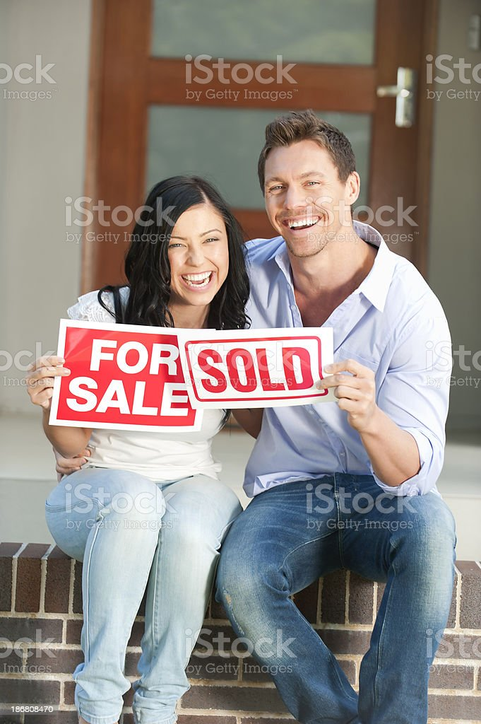 Happy couple holding for sale and sold signs royalty-free stock photo