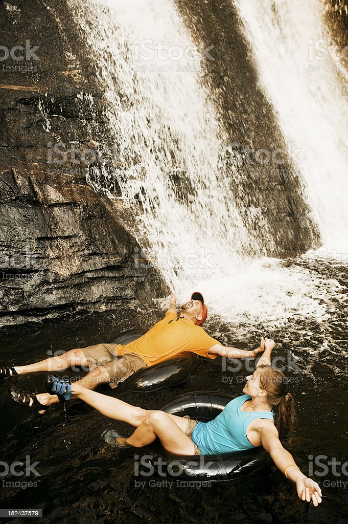 Happy Couple Holding Hands and Inner Tubing royalty-free stock photo