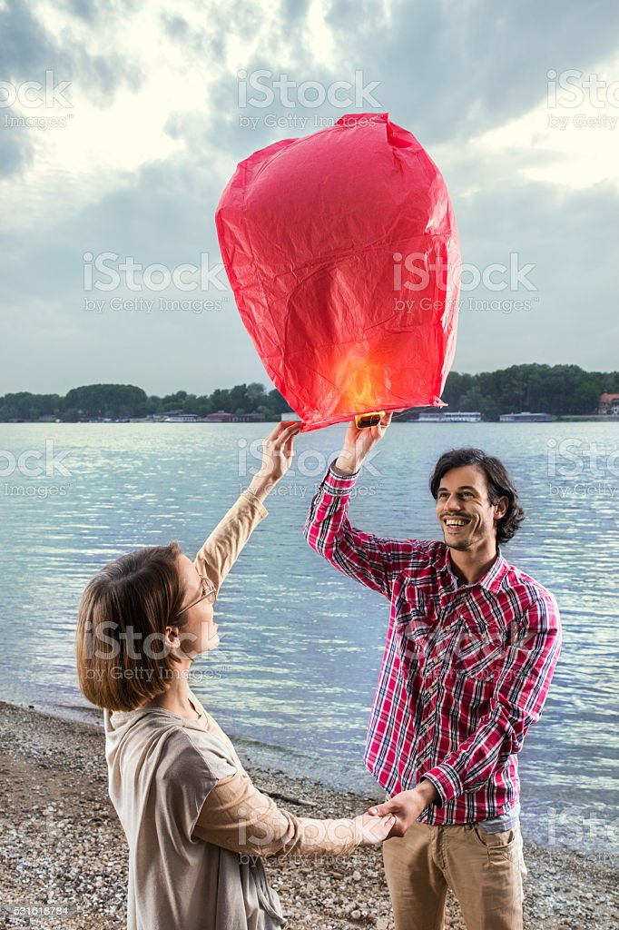 Happy couple holding hands and releasing Chinese lantern outdoors. stock photo