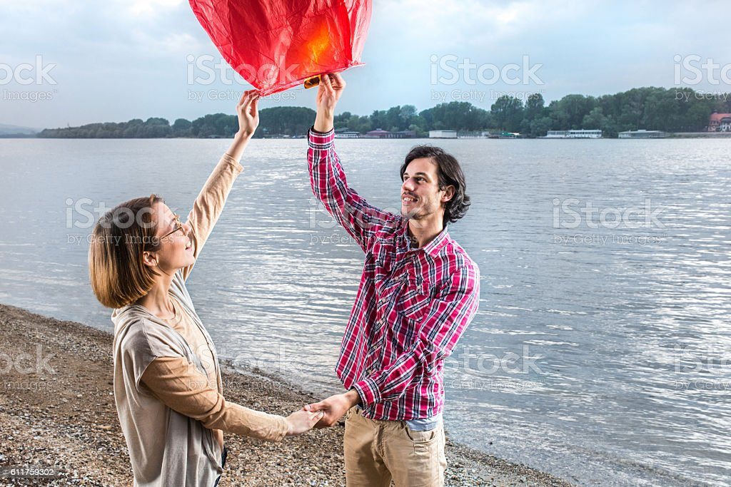 Happy couple holding hands and releasing lampion in the air. stock photo