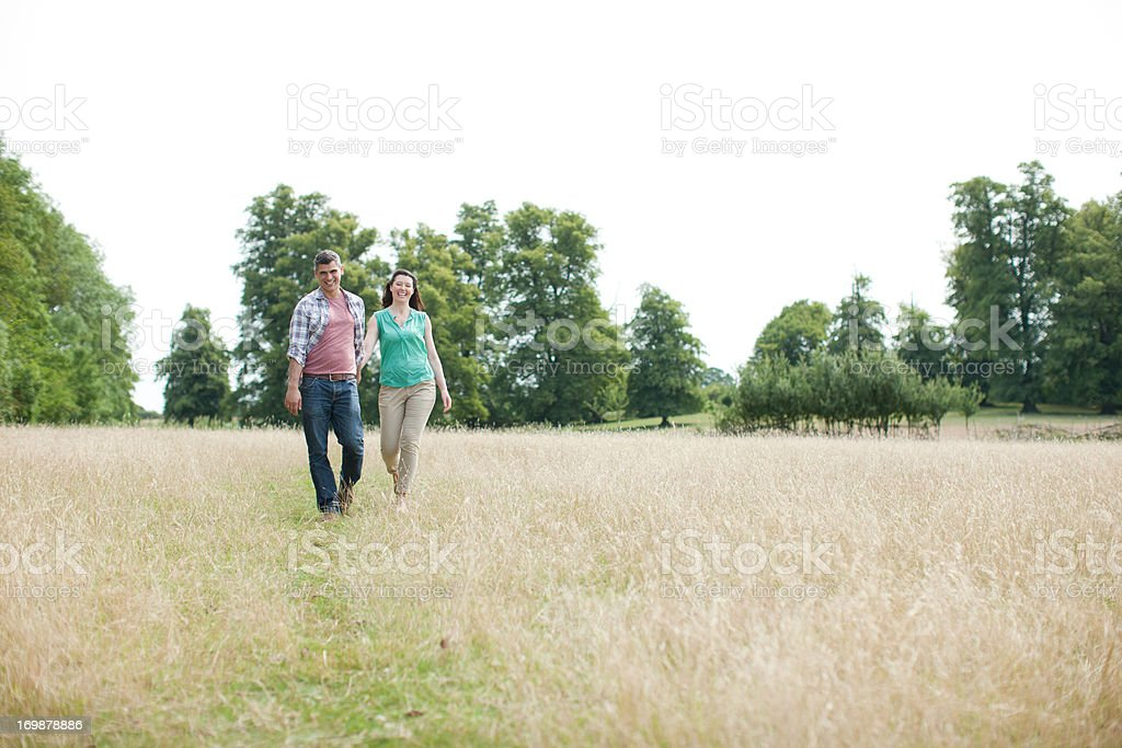 Happy couple holding hands in rural field royalty-free stock photo