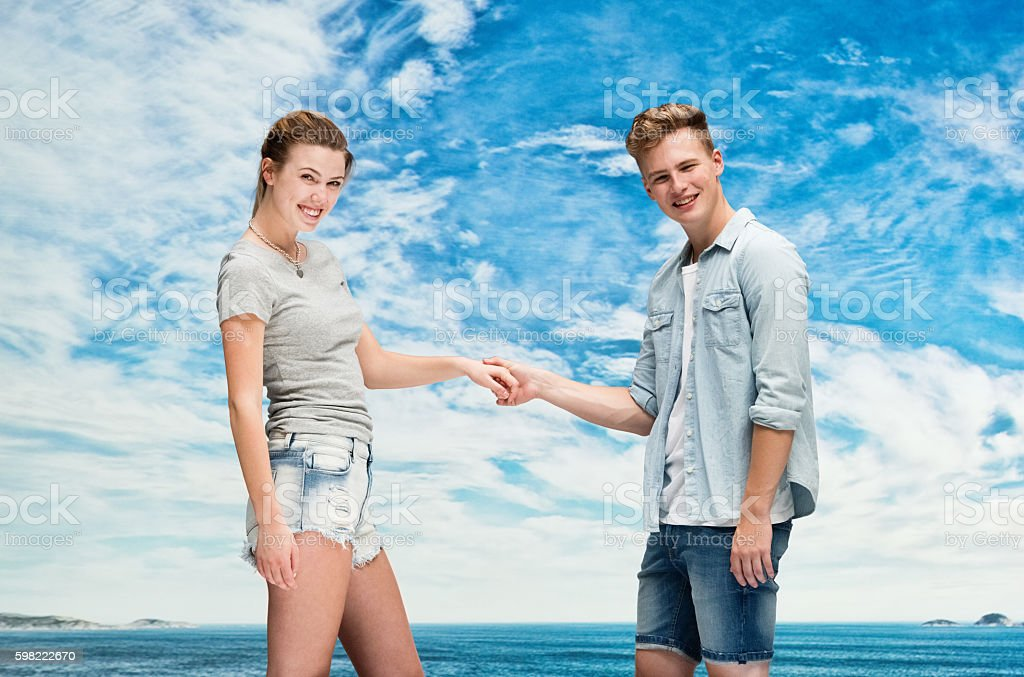 Happy couple holding hands outdoors stock photo