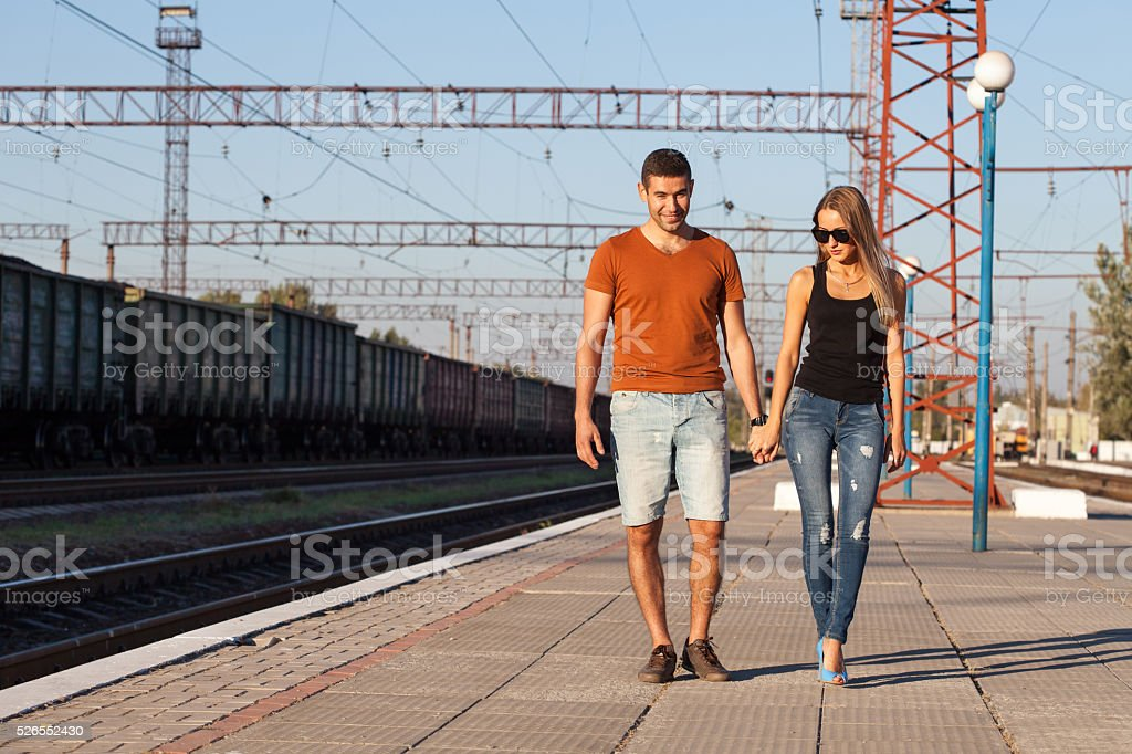 Happy couple holding hands, walking on railway station in summer stock photo