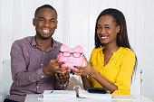 Happy Couple Holding Piggybank