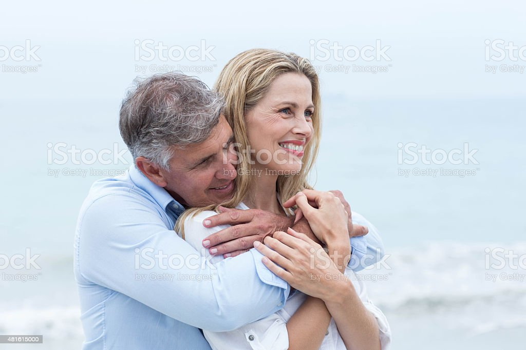 Happy couple hugging each other by the sea stock photo