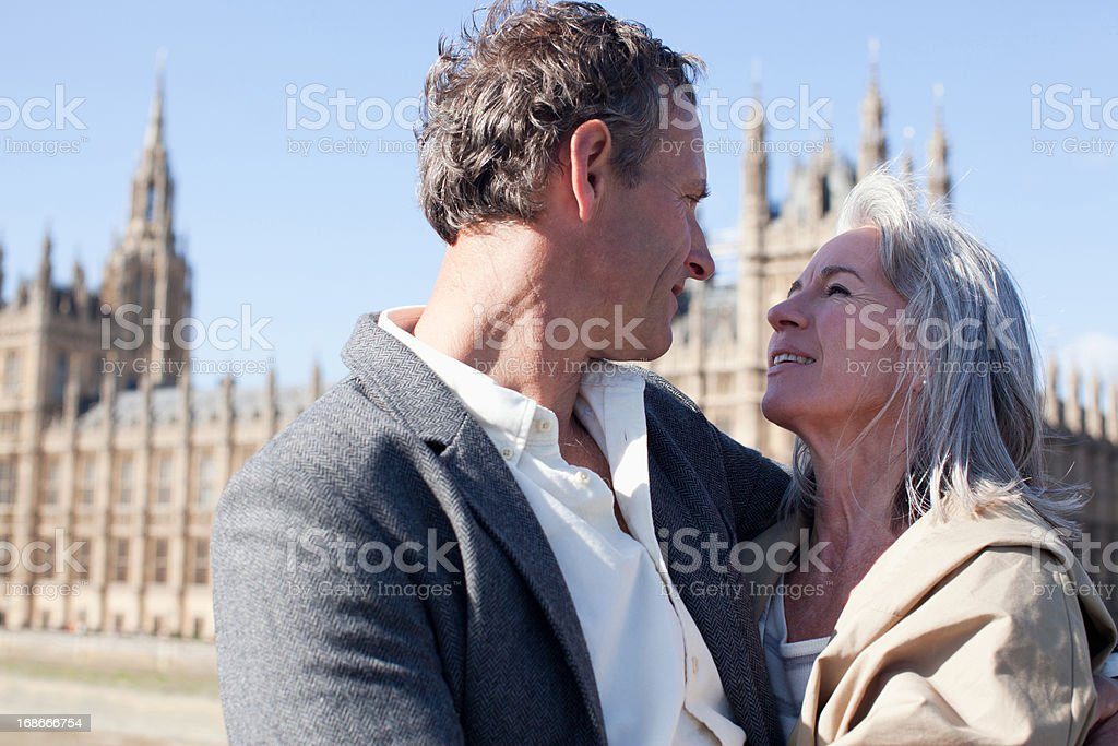 Happy couple hugging in front of Parliament Buildings in London royalty-free stock photo