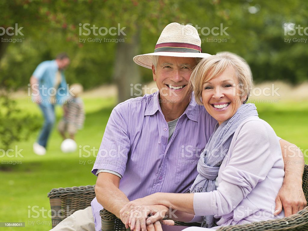 Happy couple in garden with people in the background royalty-free stock photo