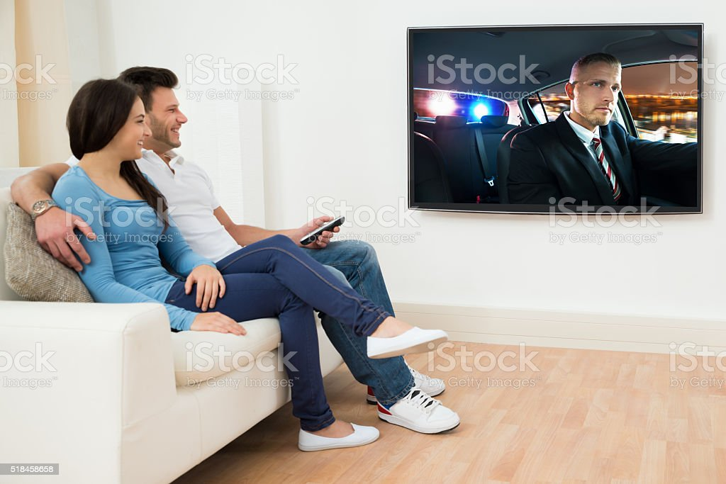 Happy Couple In Livingroom Watching Movie stock photo