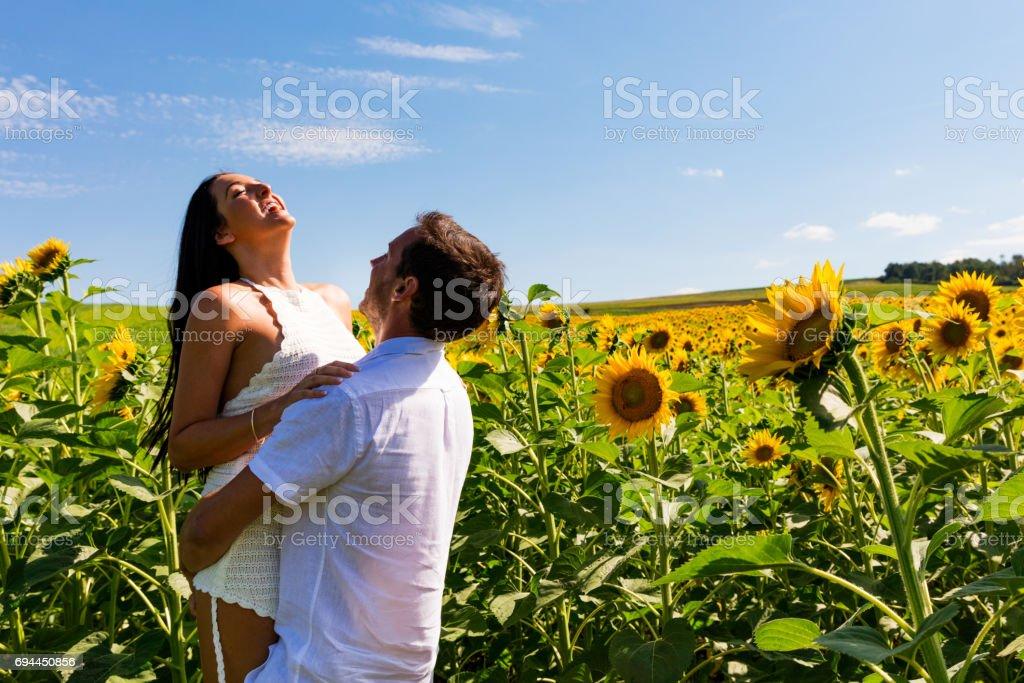 Happy couple in sunflower field stock photo