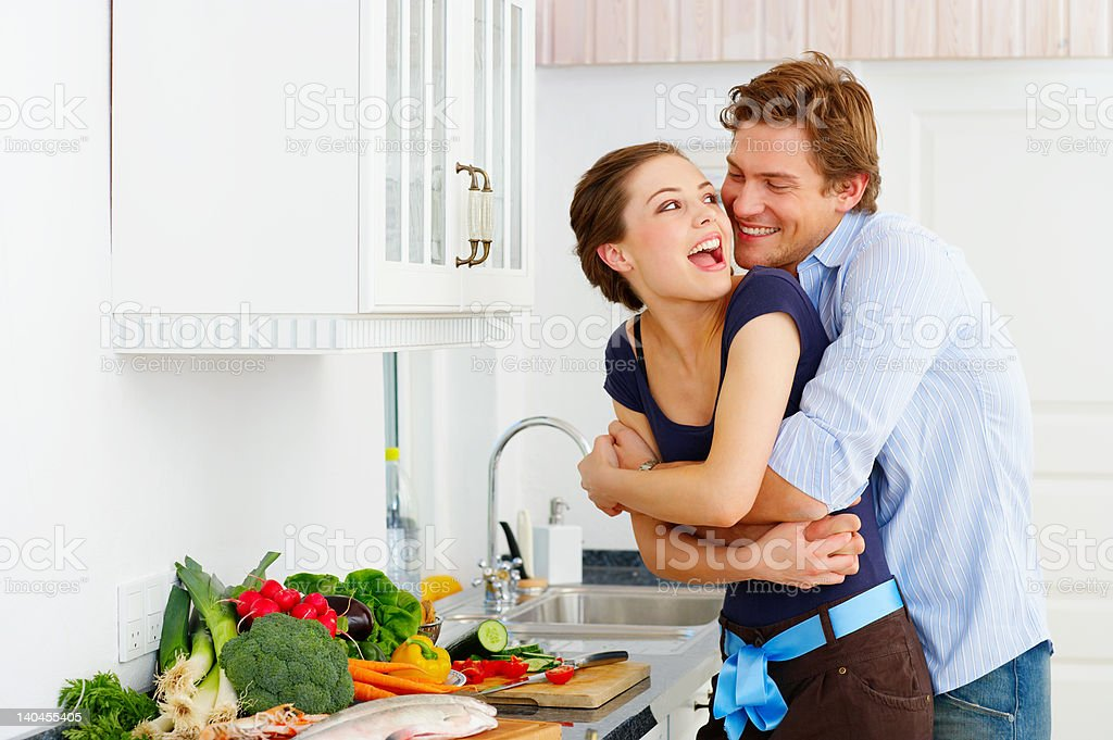 Happy couple in their kitchen royalty-free stock photo
