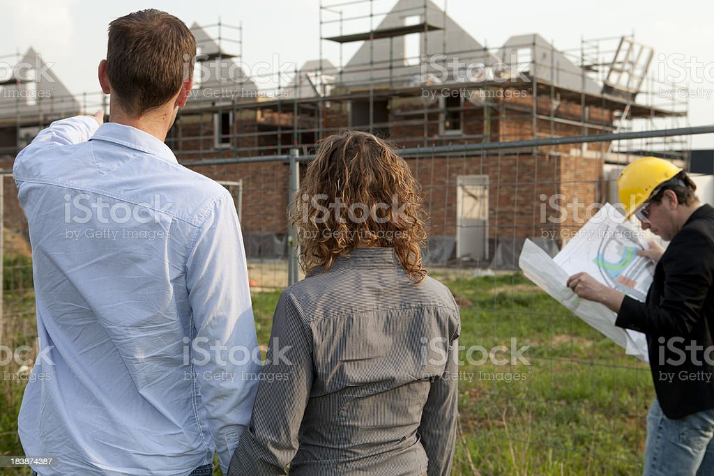 Happy couple is looking at their new home. royalty-free stock photo